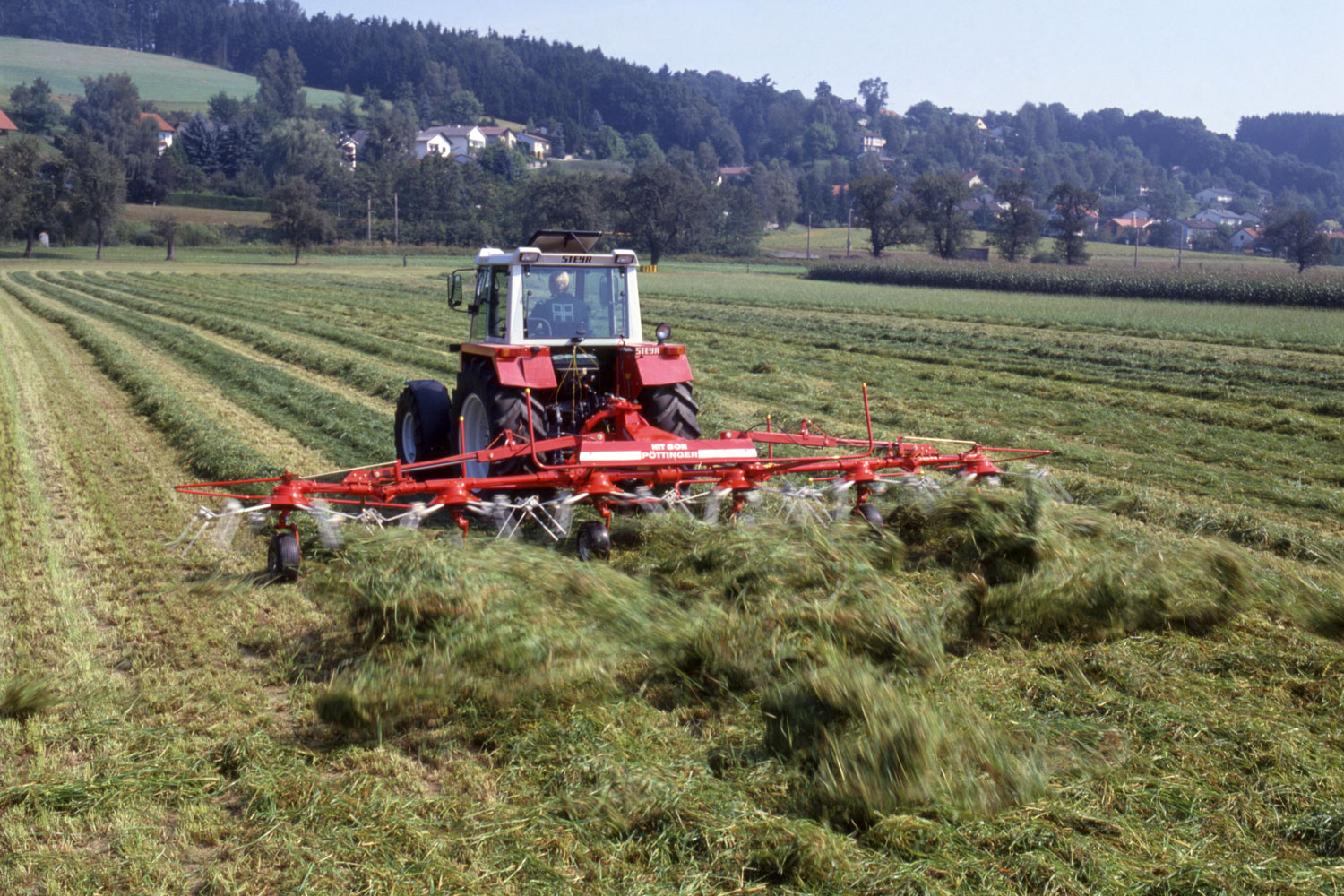A familiar picture with the aroma of fresh hay: Tedding with a PÖTTINGER HIT tedder.